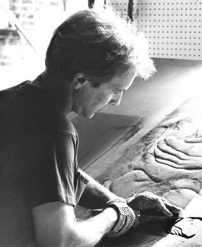 Image of Biehl carving slate bas-relief with hand chisel.