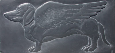 Image of slate carving representing winged dachsund